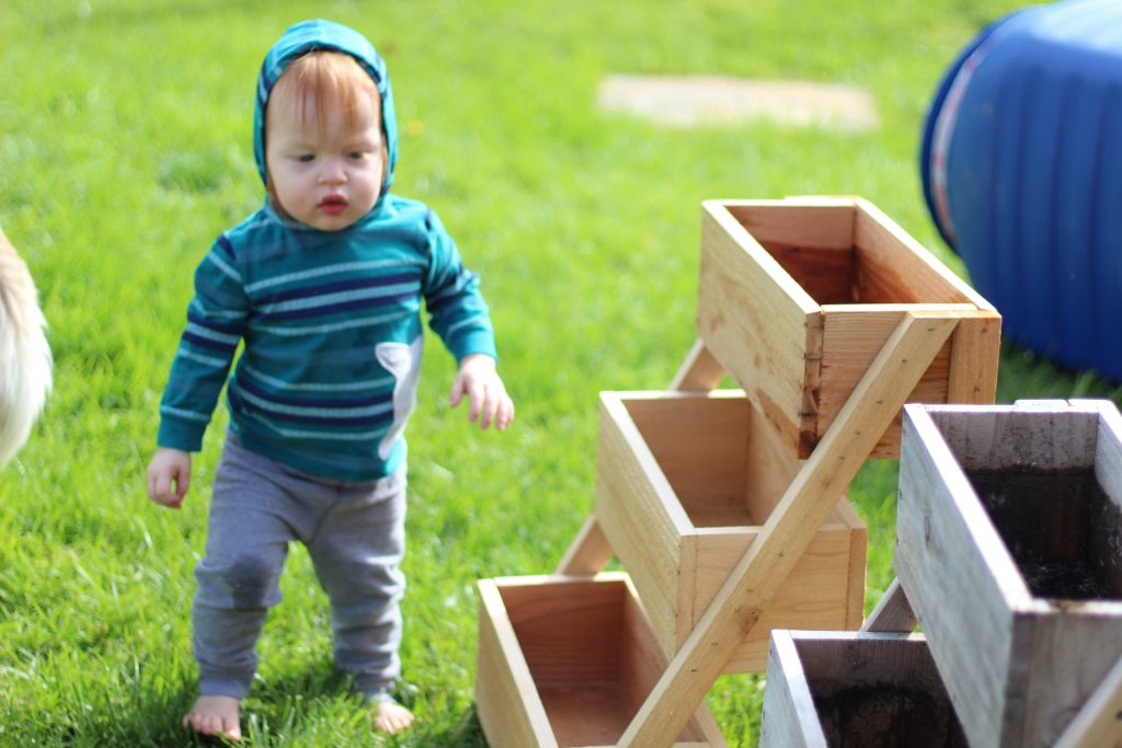 small child with a wood planter