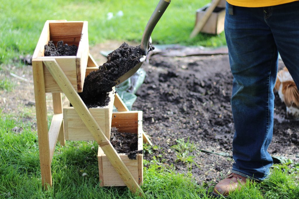 putting dirt in wooden planter